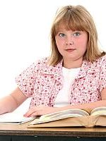 cute little school girl sitting in desk with books